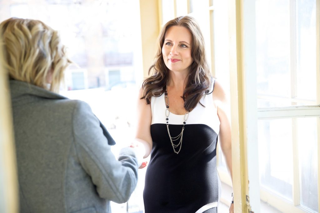 Professional woman shaking another woman's hand in an interview setting. Image used to describe the podcast episode: 9 Killer Resume Statistics to Help you Win an Interview.